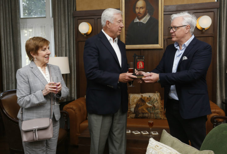 Dean Mark Taylor offers a token of appreciation—a miniature Bear pub sign—to Bob and Kathleen O